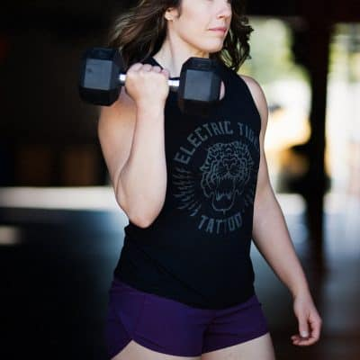 white woman with long brown wavy hair wearing a black tank top and purple shorts does a bicep curl with a dumbbell
