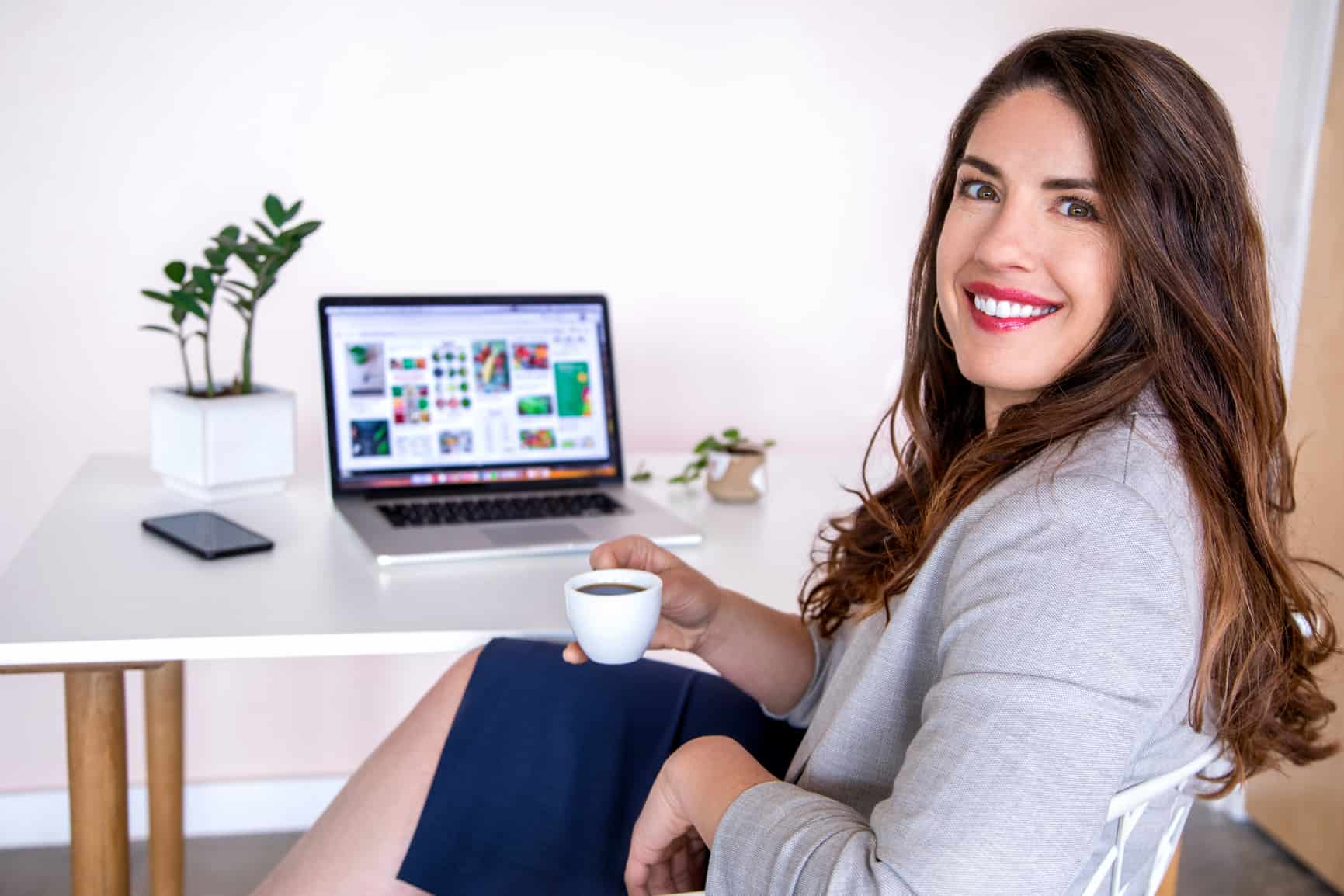white woman with long wavy brown hair wearing a tan blazer sits at a laptop computer