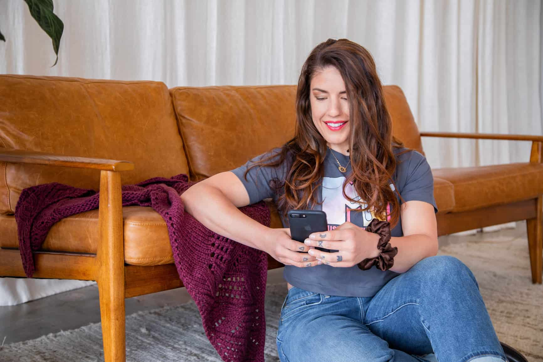 white woman with long brown wavy hair wearing a grey MTV t shirt and jeans sits in front of a leather couch holding a phone