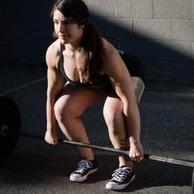 white woman with long brown wavy hair in a ponytail wearing a black tank top and black shorts holds onto a barbell about to do a dealift