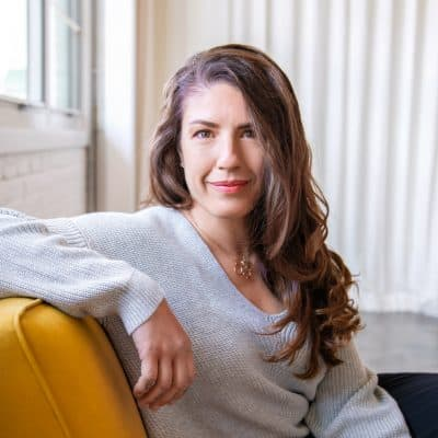 white woman with long brown wavy hair wearing grey sweater and sitting on a mustard colored couch looks directly at the camera