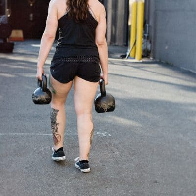 white woman with long brown wavy hair in a ponytail wearing a black tank top and short holds a kettlebell in each hand and walks away from the camera