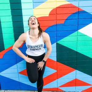 """Woman wearing white tank top and black pants stands against a colorful mural background. The shirt says """"stronger things"""" in black text."""