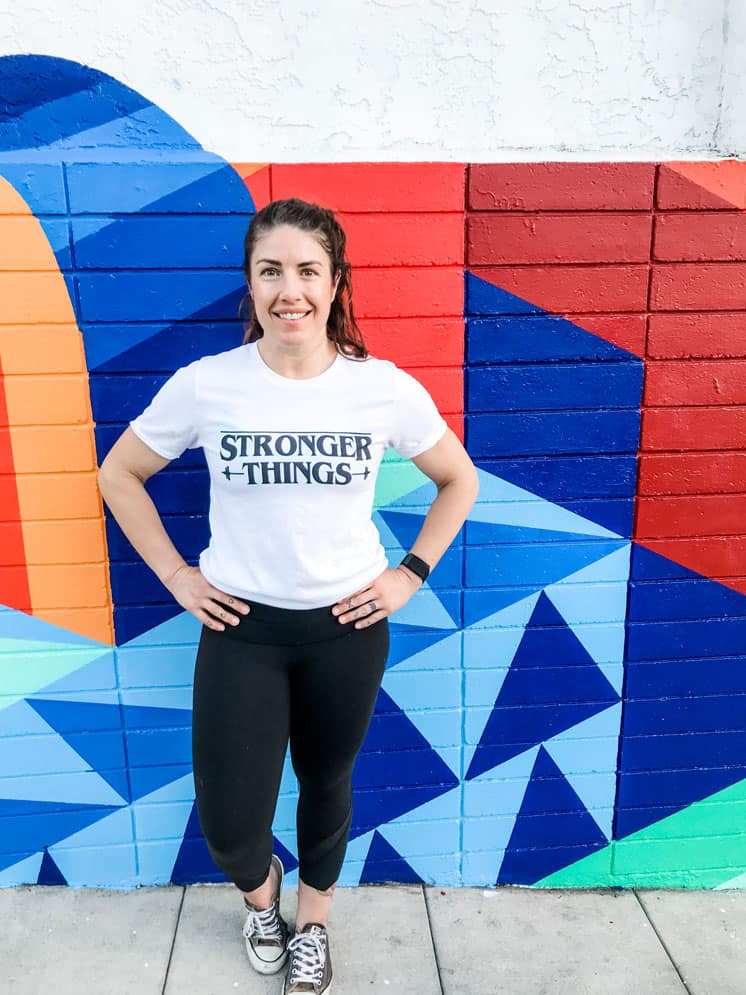 """Woman wearing white t shirt and black pants stands against a colorful mural background. The shirt says """"stronger things"""" in black text."""
