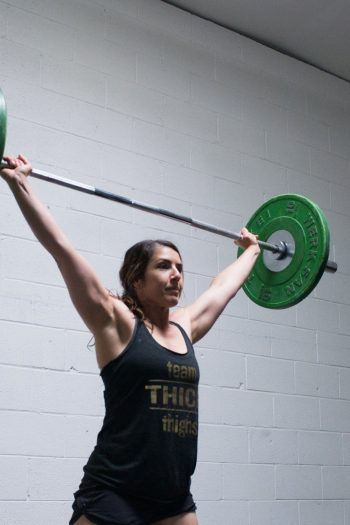 woman with brown hair hold a barbell overhead