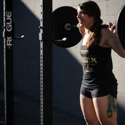white woman with brown hair dressed in tank top and shorts doing a barbell squat - low energy availability